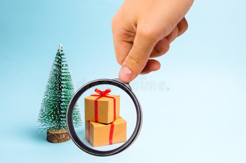 Powiększać - szkło jest przyglądający prezent na błękitnym tle i choinka minimalista Rodzinny wakacje, boże narodzenia zdjęcia royalty free