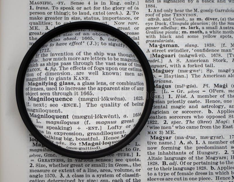Powiększać - szkło na słownik stronie przeglądać przez obiektywu obrazy royalty free
