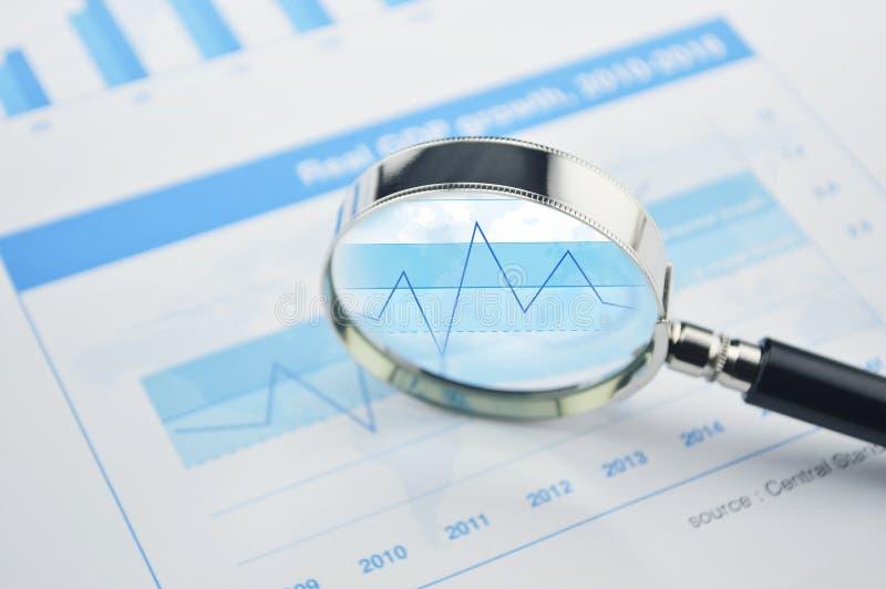 Powiększać - szkło nad pieniężnym mapy i wykresu biznesem fotografia royalty free