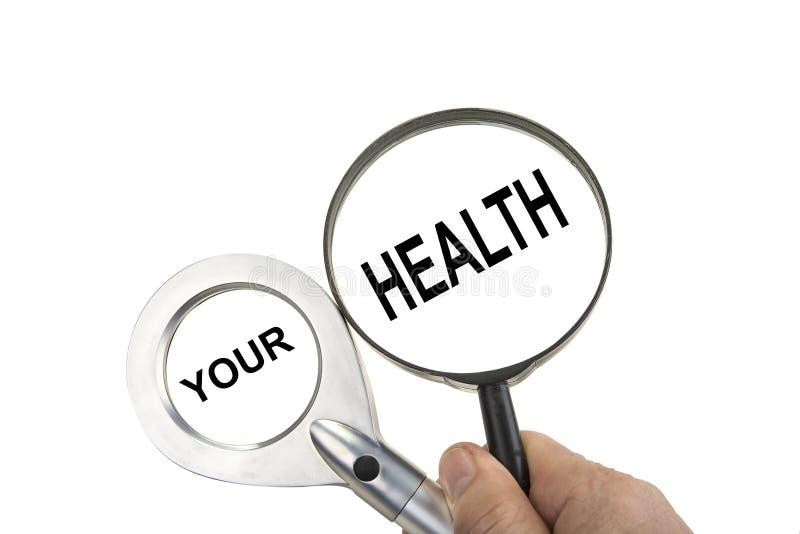 Powiększać - szkło w ręce na bielu Twój zdrowia pojęcie obraz stock