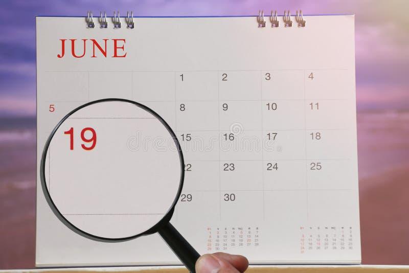 Powiększać - szkło w ręce na kalendarzu ty możesz patrzeć Nineteenth dzień zdjęcie stock