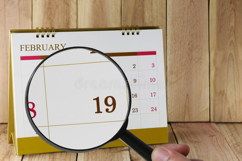 Powiększać - szkło w ręce na kalendarzu ty możesz patrzeć Nineteenth dzień obrazy royalty free
