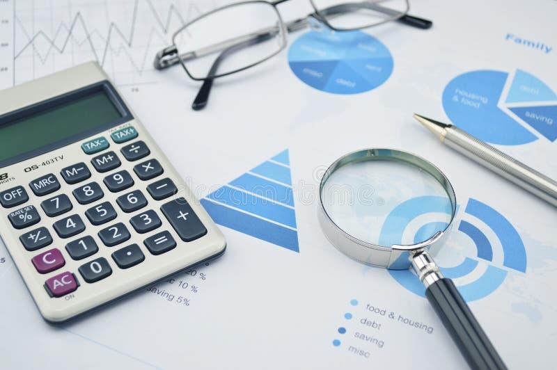 Powiększający - szkło, pióro, szkła i kalkulator na rodzinnym budżecie g, obrazy stock