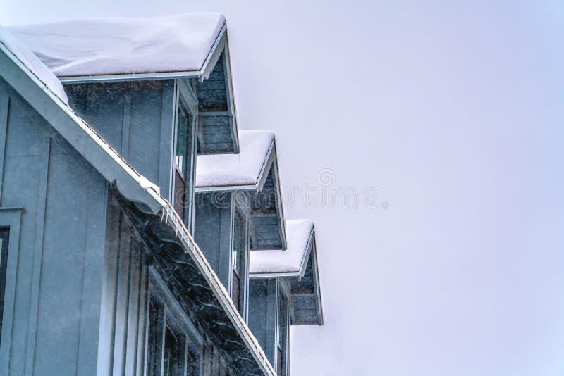 Powierzchowność dom z śnieżnym dachem przeciw niebu zdjęcia royalty free