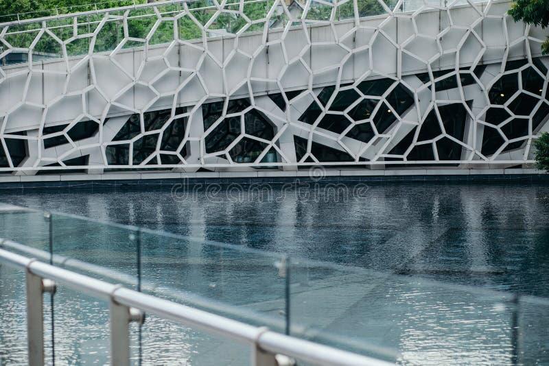 Powierzchowność nowożytny budynek z abstrakcjonistyczną siatką przy małym stawem zdjęcia royalty free