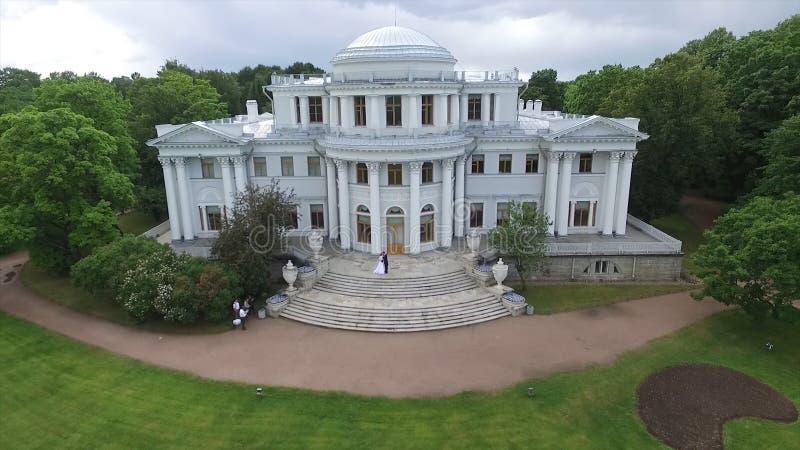 Powietrzna ankieta państwo młodzi który tanczy przy pałac w ogródzie Duży biały pałac lub kasztelu widok Latać obraz stock