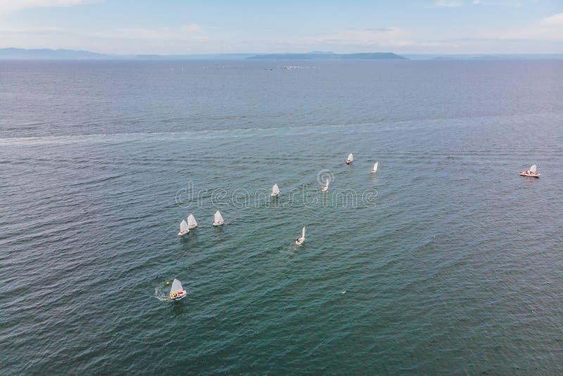 Powietrzna truteń fotografia młodzi nastolatkowie na małych żeglowanie łodziach współzawodniczy w regatta przy śródziemnomorskim  obraz royalty free