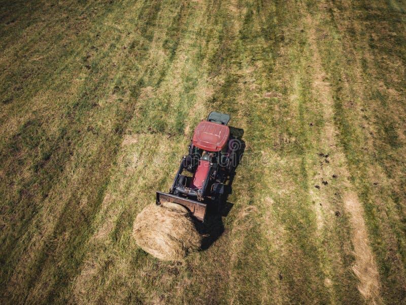 Powietrzna truteń fotografia Zbiera siano rolki w Pszenicznym polu z Czerwonym ciągnikiem rolnik - Pogodny letni dzień, rocznika  obraz stock