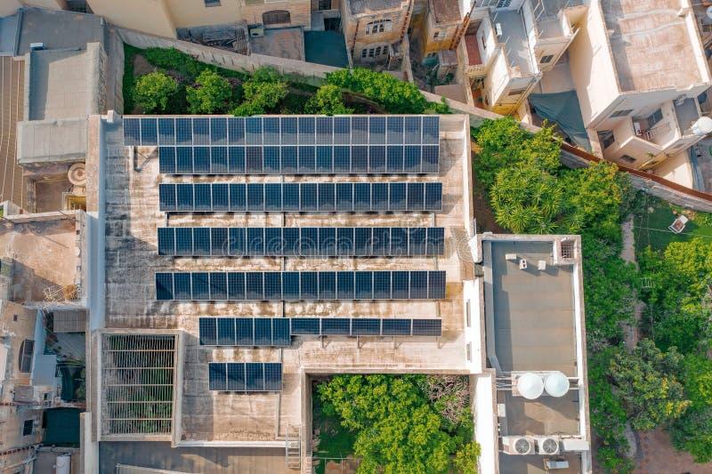 Powietrzni odgórnego widoku panel słoneczny na dachu budynek, źródło alternatywne produkcja energii, w mieście z zwartym zdjęcia stock