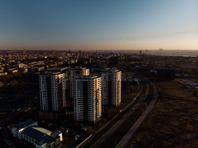 Powietrzny dramatyczny sceneria zmierzch z widokiem nad drapacz chmur w Ryskim, Latvia - Stary Grodzki śródmieście jest widoczny  zdjęcie stock