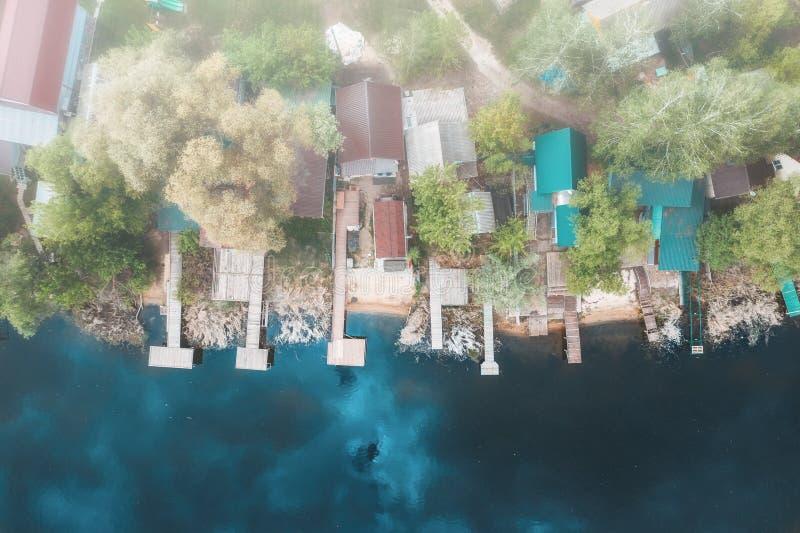 Powietrzny odgórny widok domy z molami na brzeg rzekim w mgłowym dniu, zaparowywa z góry widok obrazy stock