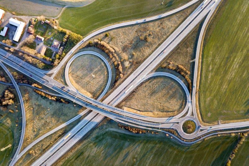 Powietrzny odgórny widok nowożytnej autostrady drogowy skrzyżowanie, domowi dachy na wiosny zieleni odpowiada tło Trute? fotograf zdjęcia royalty free