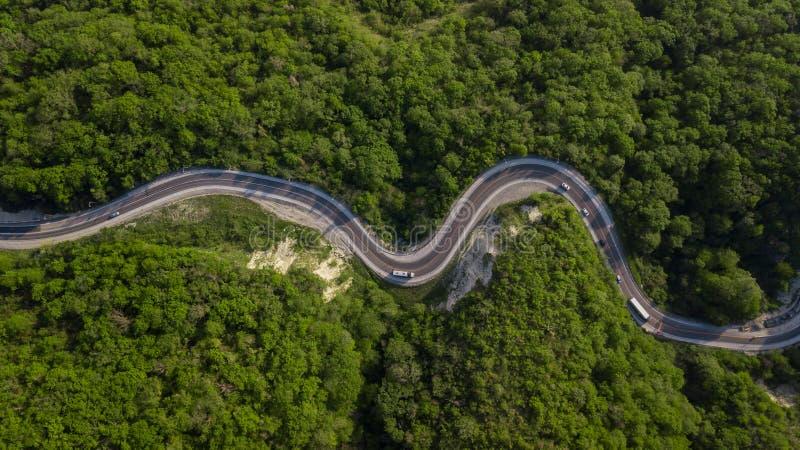 Powietrzny odgórny widok: samochodu jeżdżenie na zygzakowatej wijącej halnej drodze zdjęcie royalty free