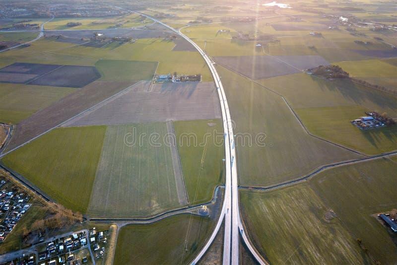 Powietrzny odgórny widok wiejski krajobraz, nowożytna autostrady droga i mali rolni budynki na wiosny zieleni, odpowiadamy tło tr obrazy stock