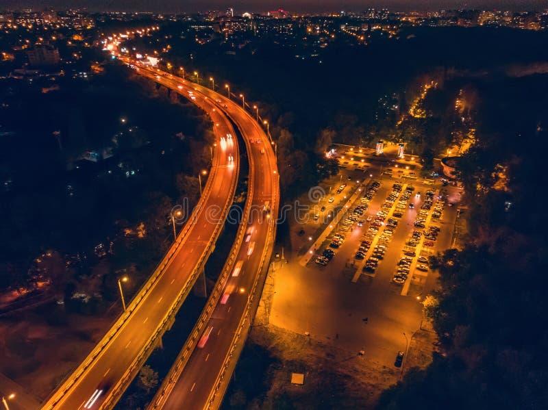 Powietrzny panoramiczny widok od above nocy miasto z mostem, drogą z samochodowym ruchem drogowym i parking dla samochodów, trute zdjęcia royalty free