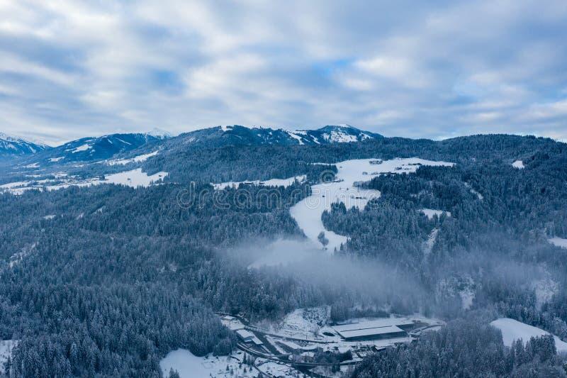 Powietrzny trutnia widok droga przez lasowej wysokości w w górę gór w zimie zdjęcia stock