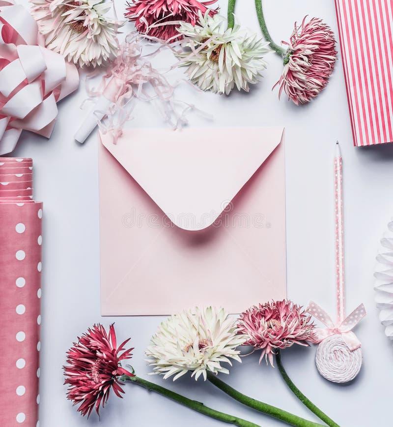 Powitania mieszkanie kłaść z pastelowych menchii kopertą, pisze, kwiaty, faborek i akcesoria na białym biurku, zdjęcia royalty free