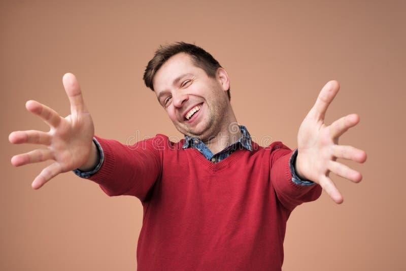 Powitanie, ładny widzieć ciebie Mężczyzna patrzeje kamerę z nastroszonymi rękami i szczęściem w czerwonym pulowerze obraz stock