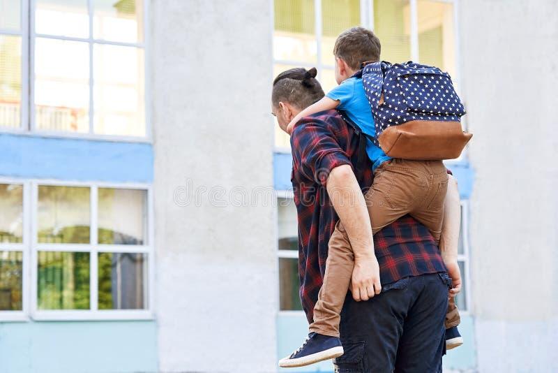 Powrót do szkoły Szczęśliwy ojciec i syn chodzą do szkoły podstawowej zdjęcia royalty free