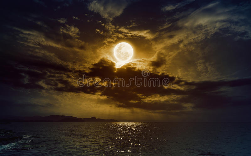 Powstający żółty księżyc w pełni w ciemnym nocnym niebie z odbiciem w wacie zdjęcia stock