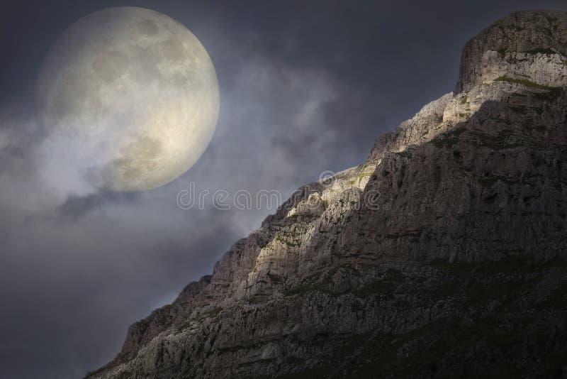 Powstający księżyc w pełni nad skalistym szczytem zdjęcia royalty free