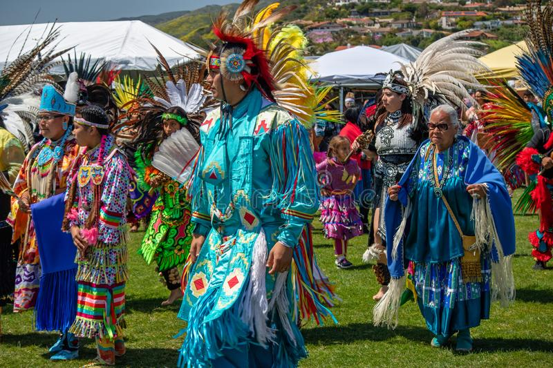 Powwow native participants moving in circle by traditional dance with their style and regalia. royalty free stock photos