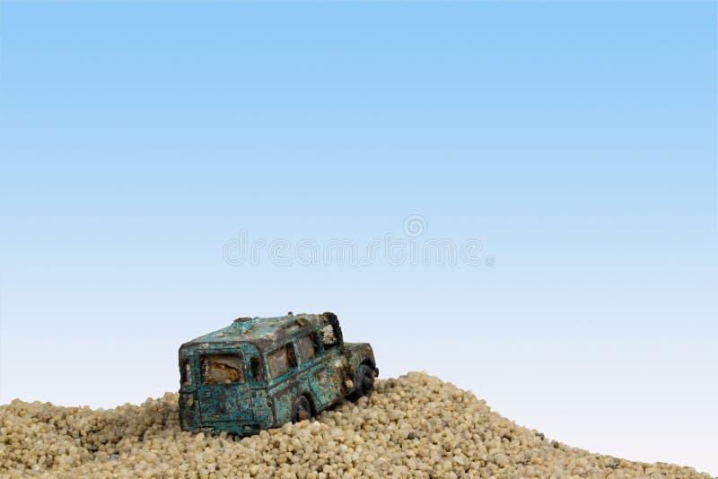 Powyginany błękit zabawki samochód w piasek jamie Przeciw niebieskiemu niebu fotografia stock