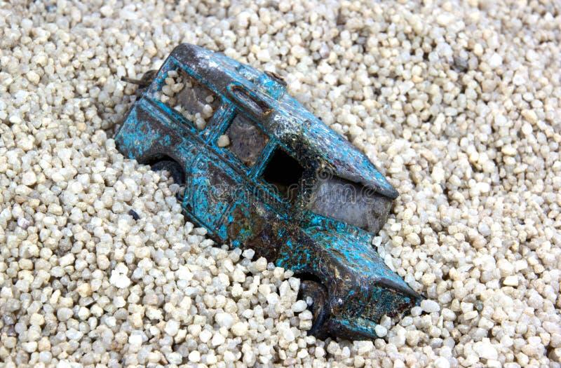 Powyginany błękit zabawki samochód w piasek jamie Przeciw niebieskiemu niebu zdjęcia stock