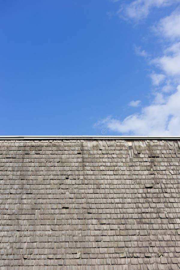 Powyginany drewniany gontu dach przeciw niebieskiemu niebu z chmurami obraz stock