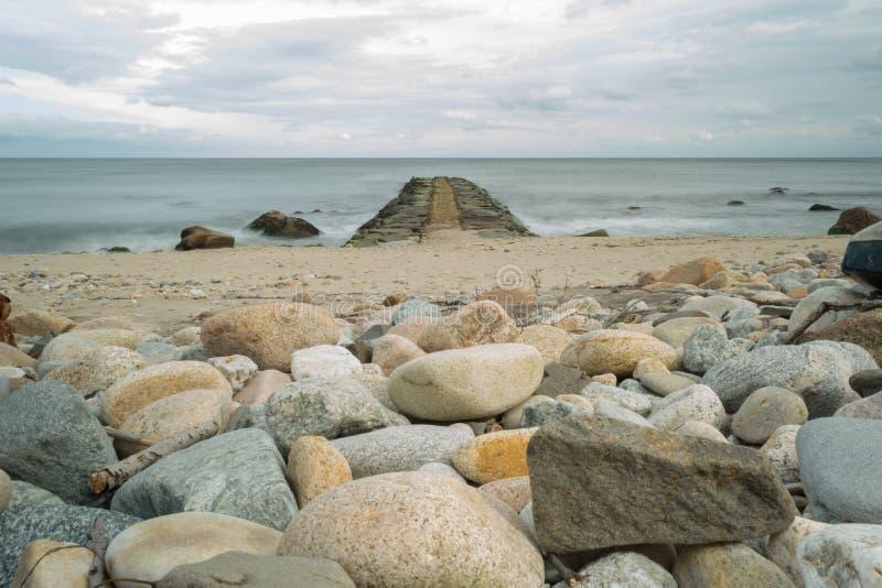 Poziom terenu strzał głazy na plaży i skalisty jetty wskazuje w kierunku horyzontu, Blokowa wyspa, RI zdjęcie royalty free