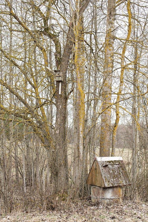 Pozo de agua viejo cerca de los árboles y de la pajarera imágenes de archivo libres de regalías