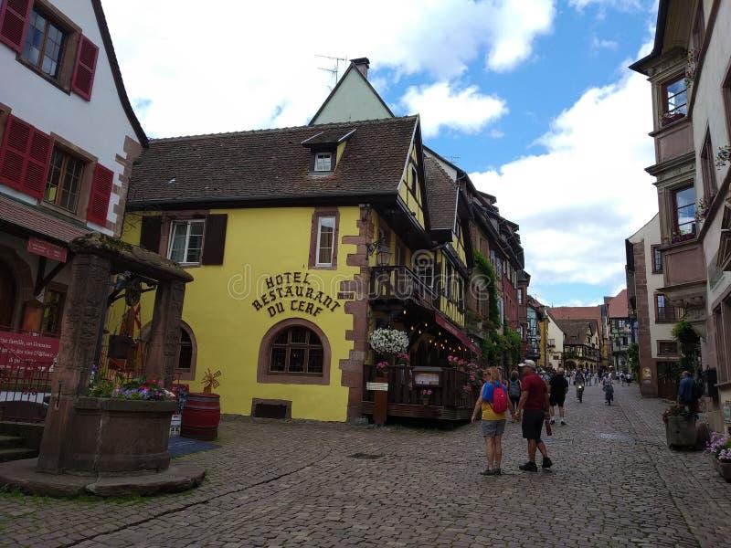 Pozo viejo adornado con las flores y las casas con las fachadas coloridas en las calles de Riquewihr imagen de archivo libre de regalías