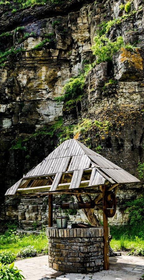 Pozo viejo cerca de la roca imagen de archivo