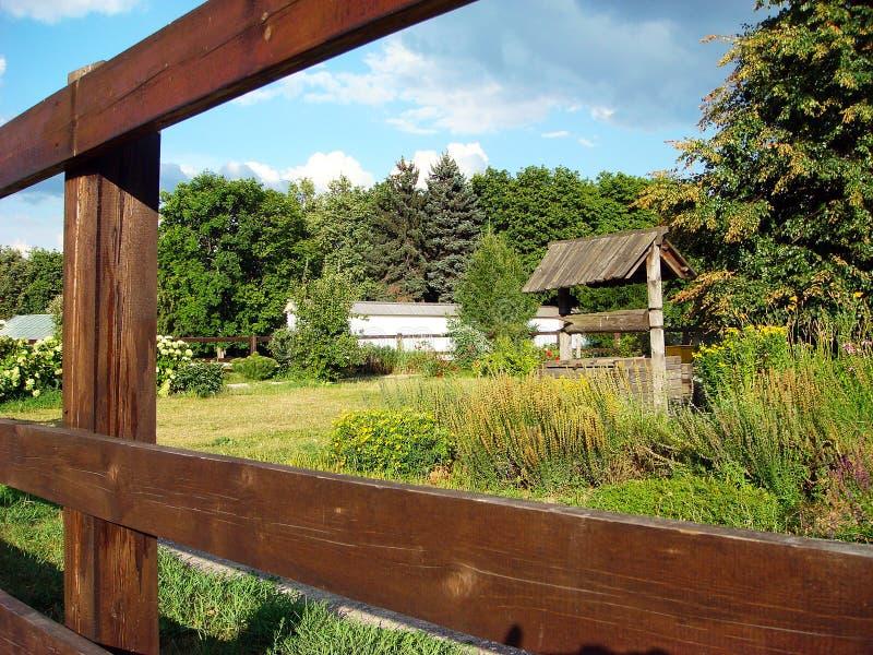 Pozo y casa rurales de agua detrás de la cerca de madera vieja imagen de archivo libre de regalías