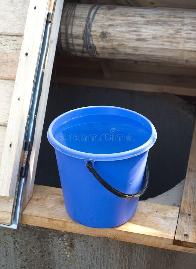 Pozo y cesta por completo de agua imagen de archivo libre de regalías