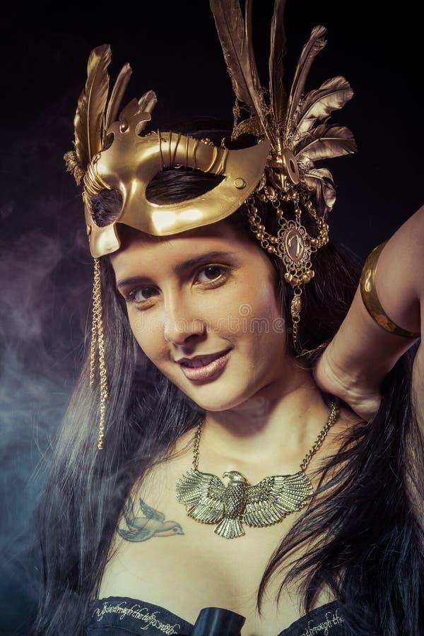 Pozować wojownik kobiety z złoto maską, długie włosy brunetka. Dłudzy brzęczenia obrazy stock