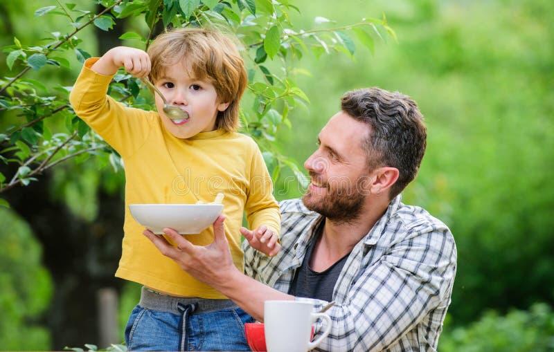 Pozwól, że ci pomogę. czas odpoczynku dla rodziny szczęśliwi ojcowie Mały chłopiec z tatą je płatki Rano śniadanie obrazy royalty free