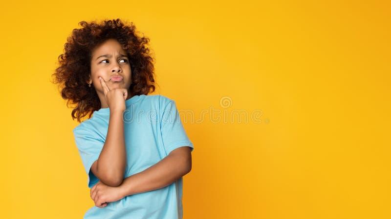 pozwól mi pomyśleć Wątpliwa, rozważna dziecko dziewczyna pozuje nad tłem, fotografia stock