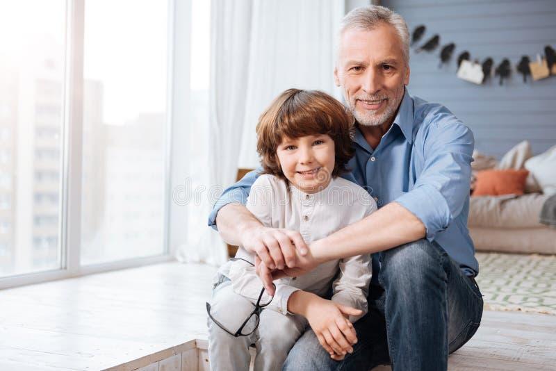 Pozytyw starzejący się mężczyzna ściska jego wnuka zdjęcia stock