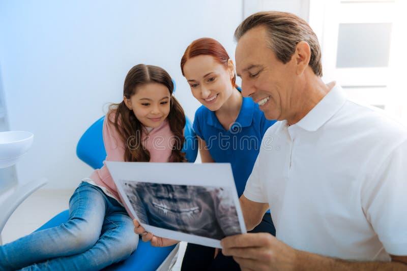 Pozytywna ładna lekarka pokazuje X promienia fotografię jego pacjenci zdjęcie royalty free