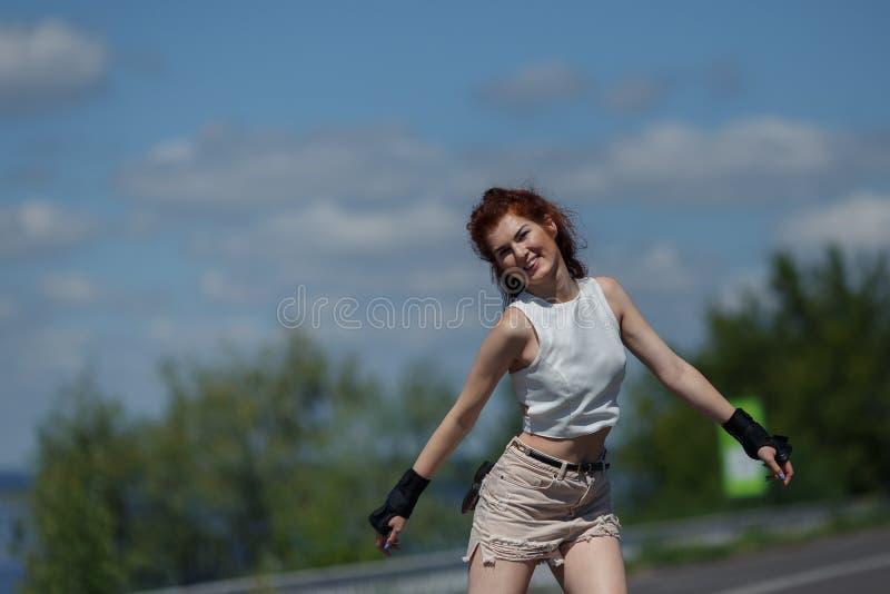 Pozytywna ładna młoda dziewczyna w skrótach i wierzchołkach jeździć na łyżwach na rolkowych łyżwach obrazy stock