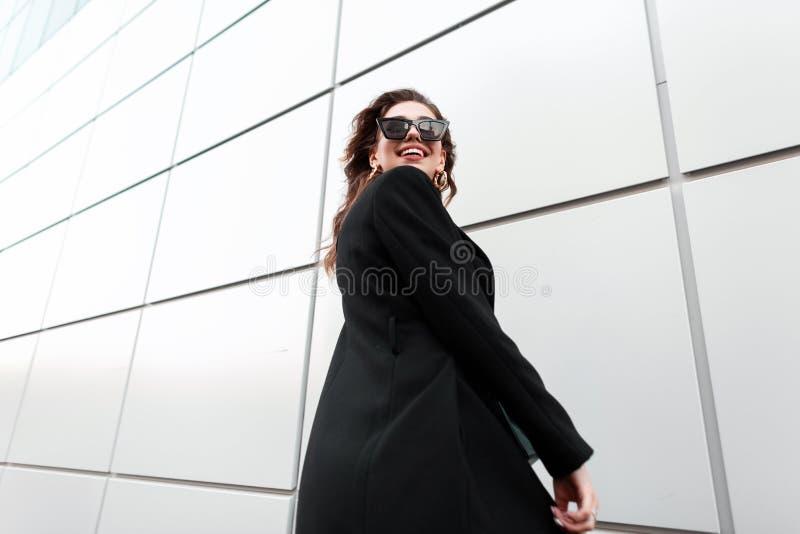 Pozytywna ładna młoda elegancka modniś kobieta w modnych ciemnych okularach przeciwsłonecznych w eleganckiego czerni długim żakie obrazy stock