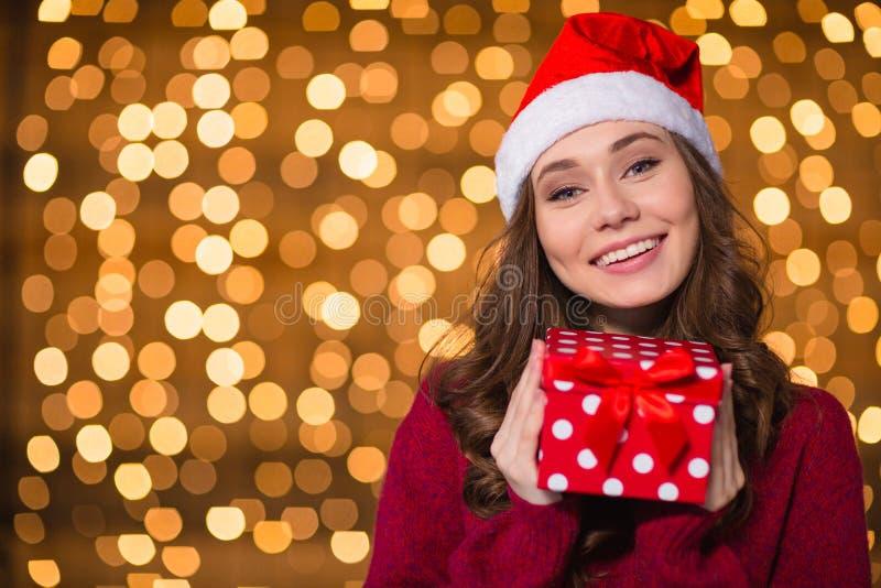 Pozytywna śliczna dziewczyna w Santa Claus kapeluszu z małą teraźniejszością zdjęcia royalty free