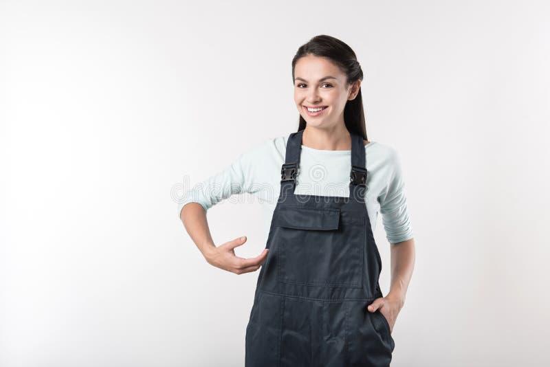 Pozytywna żeńskiego pracownika pozycja przeciw popielatemu tłu zdjęcie stock