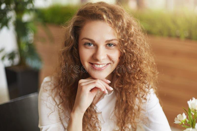 Pozytywna atrakcyjna dobra przyglądająca młoda kobieta interesującego pojawienie, kędzierzawego włosy i zdrową skórę, pozy przy k zdjęcie royalty free