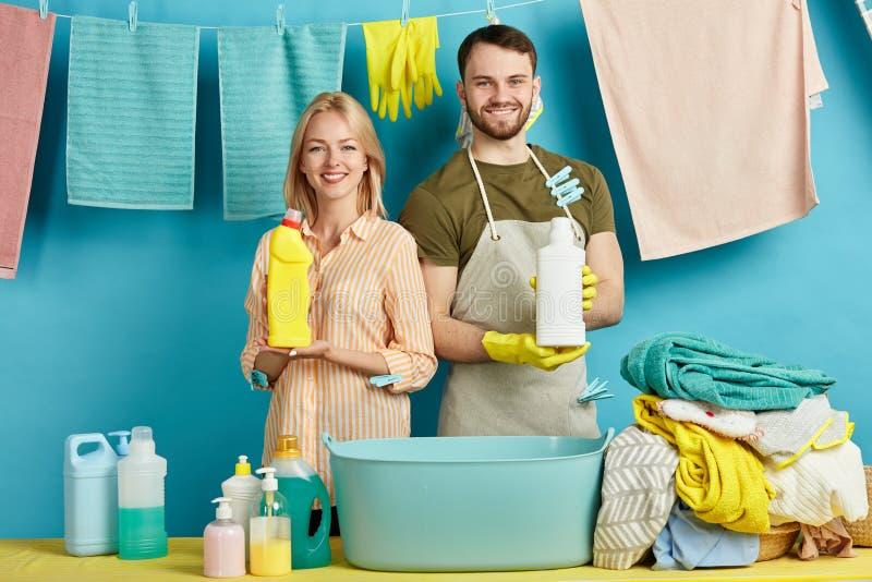 Pozytywna blondynki kobieta i przystojny brodaty mężczyzna reklamuje wydajnych detergenty obraz stock