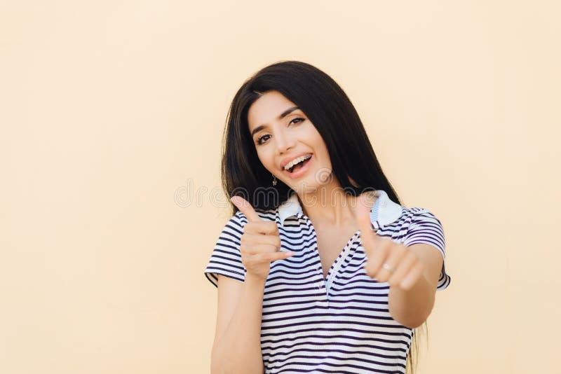 Pozytywna brunetki kobieta robi zatwierdzenie gestowi, utrzymuje kciuki podnosi, być w dobrym nastroju, raduje się coś, odizolowy zdjęcia royalty free