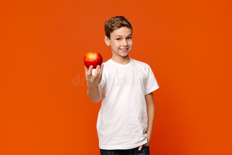 Pozytywna chłopiec oferuje świeżego czerwonego jabłka na kamerze zdjęcia stock