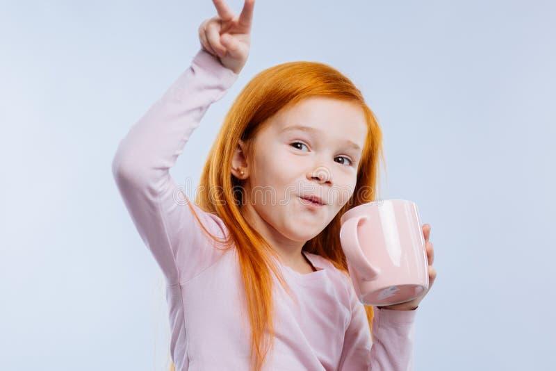 Pozytywna czerwona z włosami dziewczyna pije jej herbaty obrazy royalty free