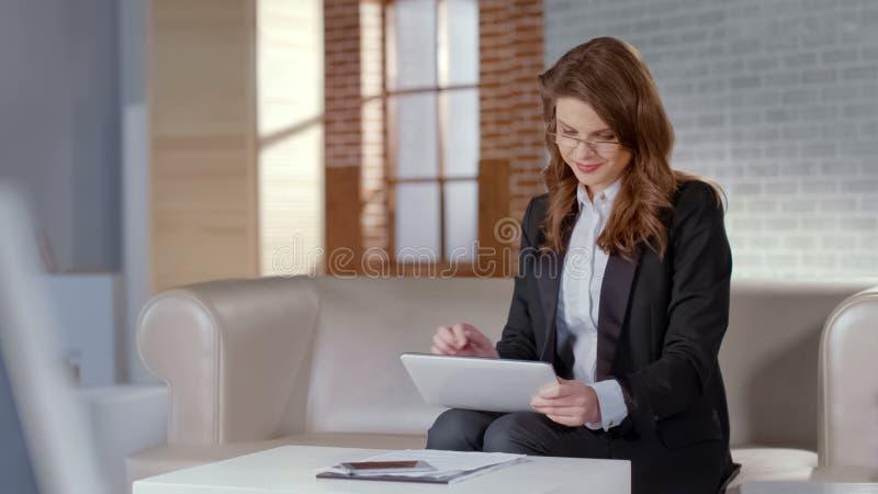 Pozytywna dama używa pastylkę dla biznesowych lub online kursów, daleka edukacja zdjęcia stock